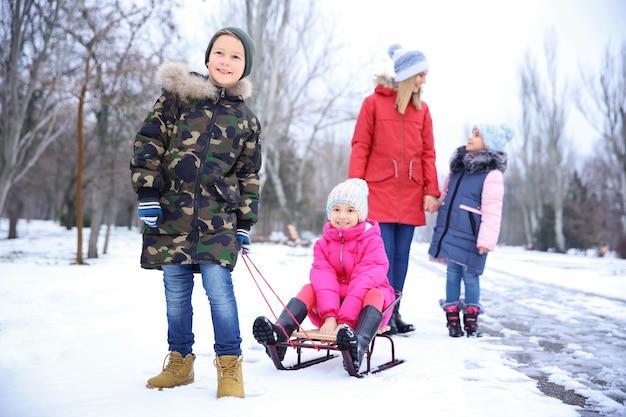 Heureuse mère avec enfants dans un parc enneigé en vacances d'hiver