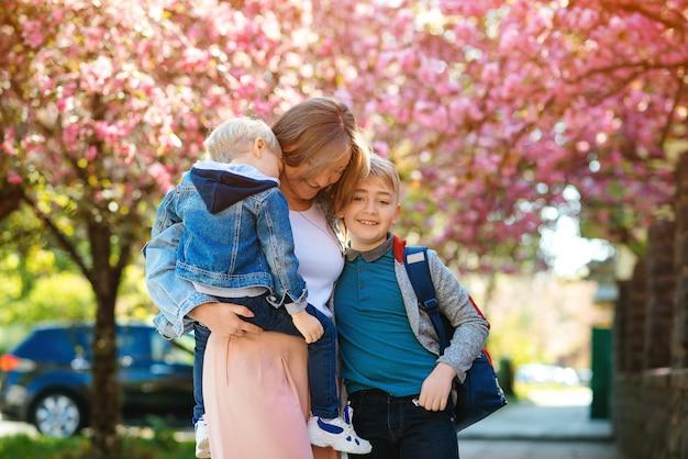 Heureuse mère avec enfants sur la promenade dans la ville de printemps. mère et enfants s'enlaçant à l'extérieur.