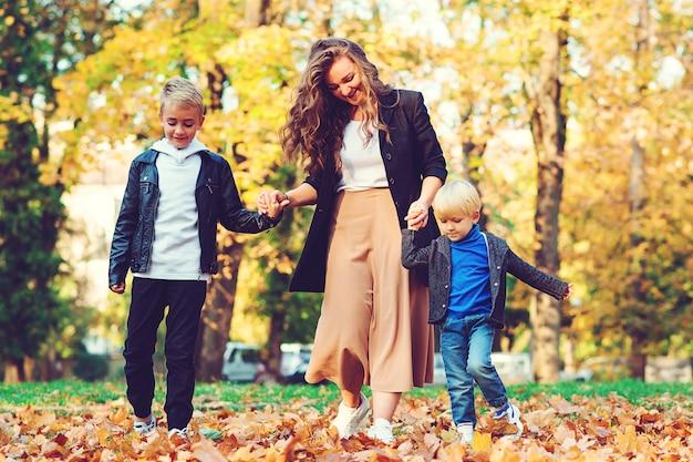 Heureuse mère et enfants s'amuser en plein air. famille à la mode marchant dans le parc en automne.