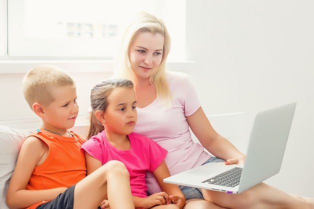 Heureuse mère et enfants utilisant un ordinateur portable numérique à la maison