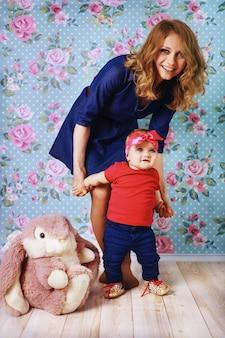 Heureuse mère enseigne à bébé à marcher.