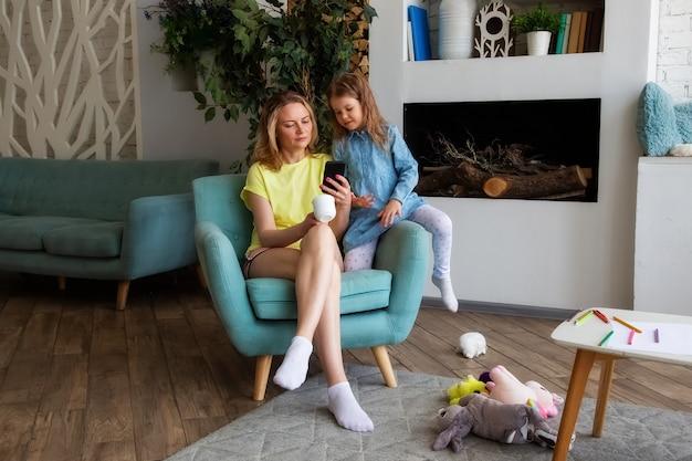 Heureuse mère est assise sur une chaise avec sa fille et regarde quelque chose de drôle au téléphone