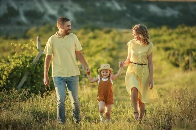 Heureuse mère de famille et bébé étreignant dans un pré fleurs jaunes sur la nature en été