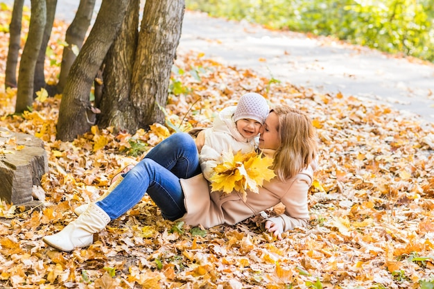 Heureuse mère de famille et bébé rire avec des feuilles dans la nature automne