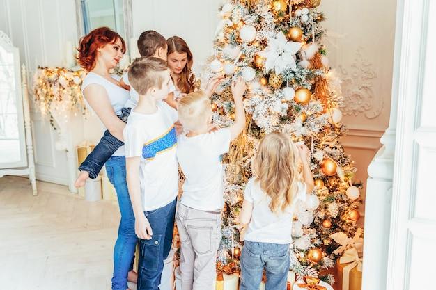 Heureuse mère de famille et cinq enfants décorant l'arbre de noël la veille de noël à la maison