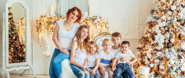 Heureuse mère de famille et cinq enfants se détendre en jouant près de l'arbre de noël à la maison