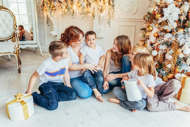 Heureuse mère de famille et cinq enfants se détendre en jouant près de l'arbre de noël