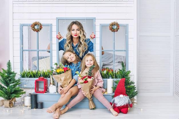 Heureuse mère de famille et deux belles filles filles en vacances en fleurs ensemble à la maison