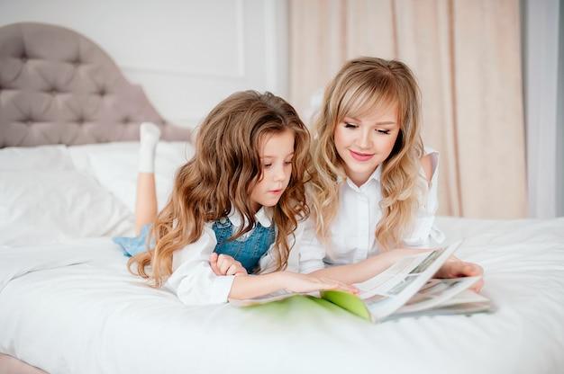 Heureuse mère de famille et enfant fille lecture tenant un livre couché dans son lit, maman souriante baby sitter racontant un conte de fées drôle à une petite fille enfant