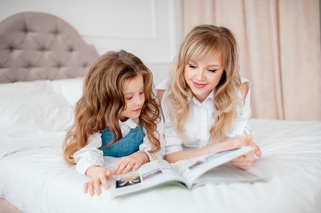 Heureuse mère de famille et enfant fille lisant tenant un livre couché dans son lit, souriant maman baby sitter racontant un conte de fées drôle à une jolie fille enfant d'âge préscolaire