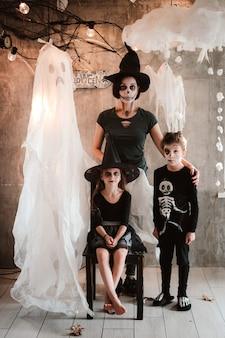 Heureuse mère de famille et enfants en costumes et maquillage à la célébration d'halloween sur le fond du paysage fantôme, fête de carnaval