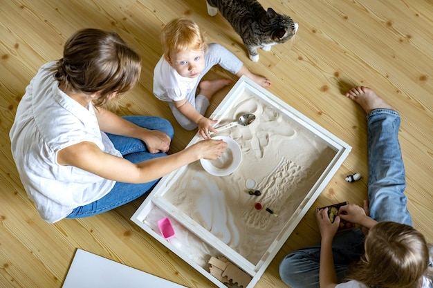 Heureuse mère de famille et enfants jouant à la maison développement de bac à sable cinétique matériaux écologiques jouets