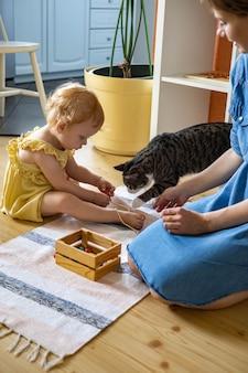 Heureuse mère de famille, fille et chat passant du temps ensemble à jouer du matériel de maria montessori
