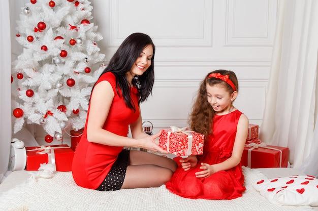 Heureuse mère de famille et fille enfant le soir de noël avec des cadeaux