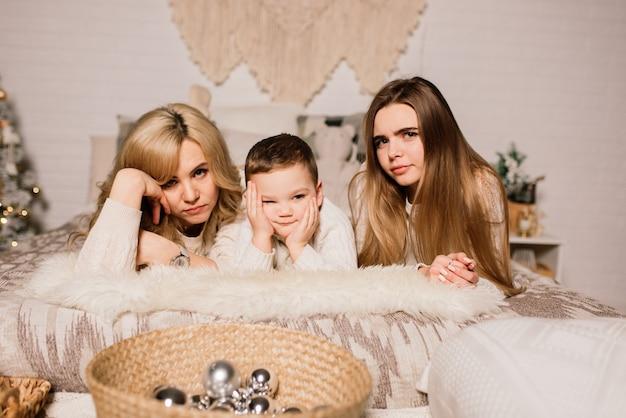 Heureuse mère de famille, fille et fils à l'arbre de noël à la maison