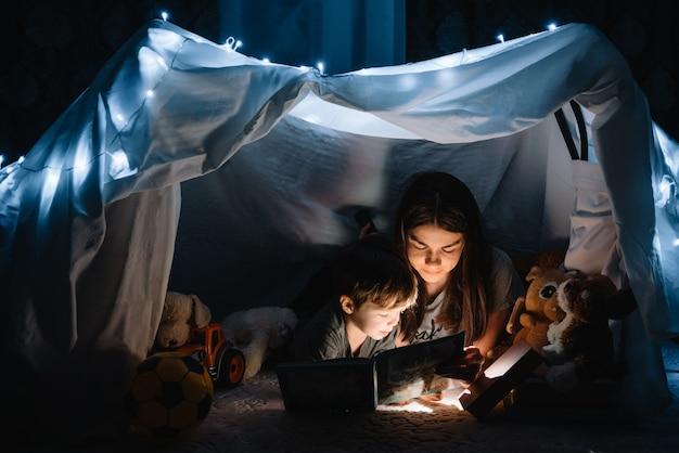 Heureuse mère de famille et fils enfant lisant un livre avec une lampe de poche dans une tente à la maison. concept de famille