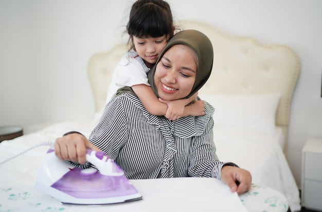 Heureuse mère de famille musulmane asiatique et petite fille repassant les vêtements