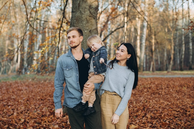 Heureuse mère de famille père et bébé sur promenade d'automne dans le parc