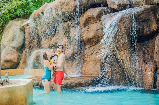 Heureuse mère de famille, père et fils se détendre sous une cascade dans un parc aquatique