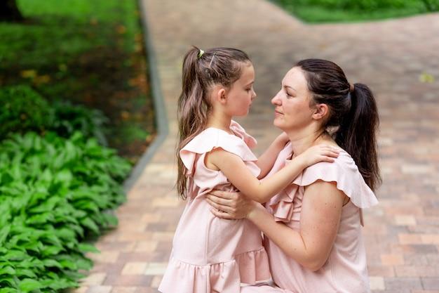 Heureuse mère et fille de 5 à 6 ans à pied dans le parc en été, la mère parle à sa fille