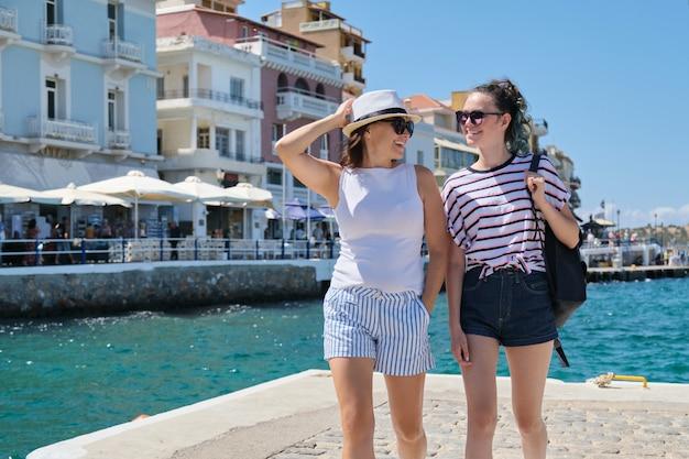 Heureuse mère et fille adolescente marchant, vacances d'été en mer