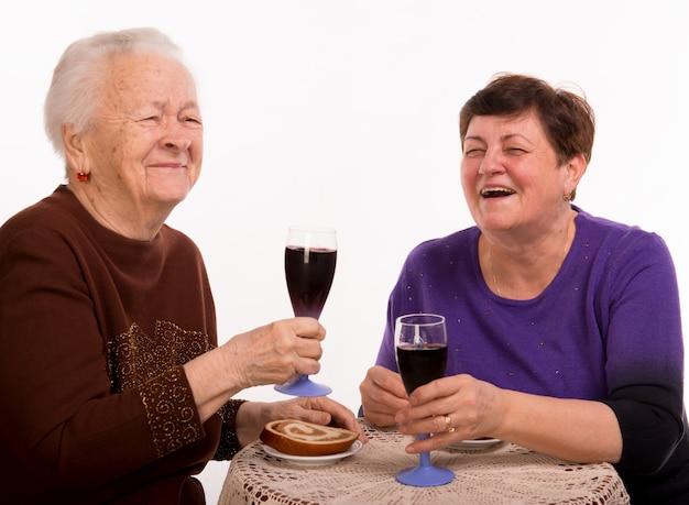 Heureuse mère avec fille, boire du vin sur un blanc