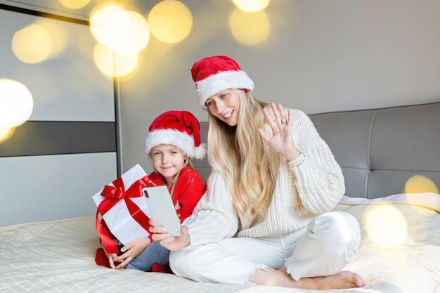 Heureuse mère et fille célébrant des amis avec appel vidéo. fête de noël en ligne