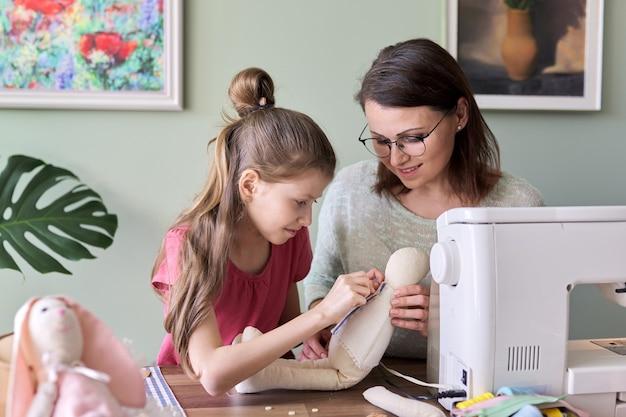 Heureuse mère et fille cousant ensemble poupée lapin jouet à la maison. famille, passe-temps et loisirs, créativité, mode de vie, compétences et apprentissage, communication parent-enfant, fête des mères
