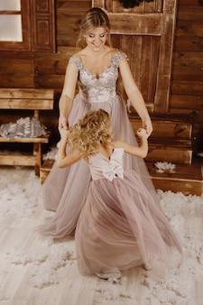 Heureuse mère et fille dansant devant une décoration de noël