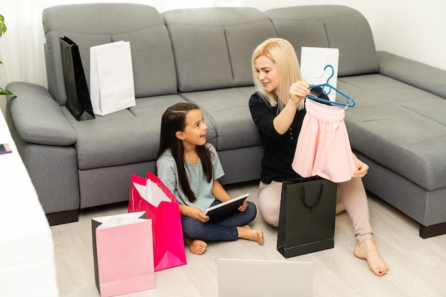 Heureuse mère et fille déballant des sacs à provisions dans le salon