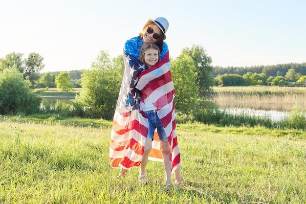 Heureuse mère et fille enfant fille étreignant sous le drapeau américain, états-unis, 4 juillet, fond de nature d'été