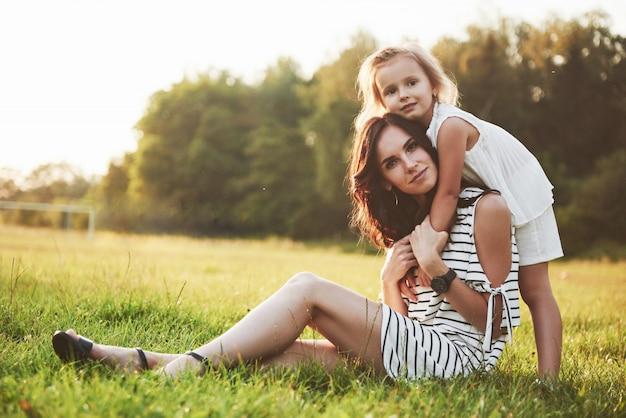Heureuse mère et fille étreignant dans un parc au soleil sur un été lumineux d'herbes.