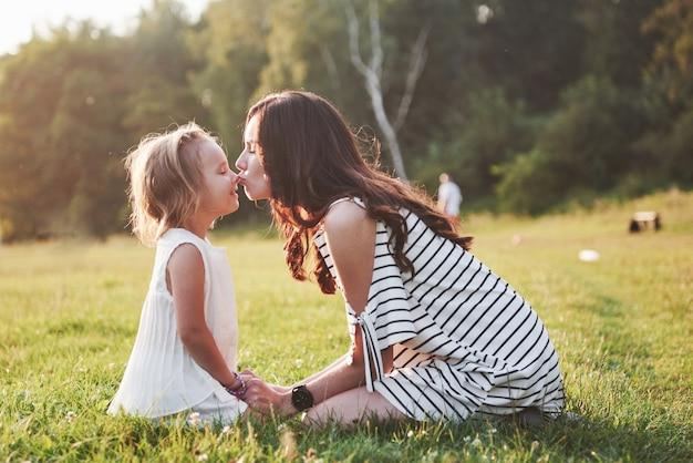 Heureuse mère et fille étreignant dans un parc au soleil sur un fond d'été lumineux d'herbes.