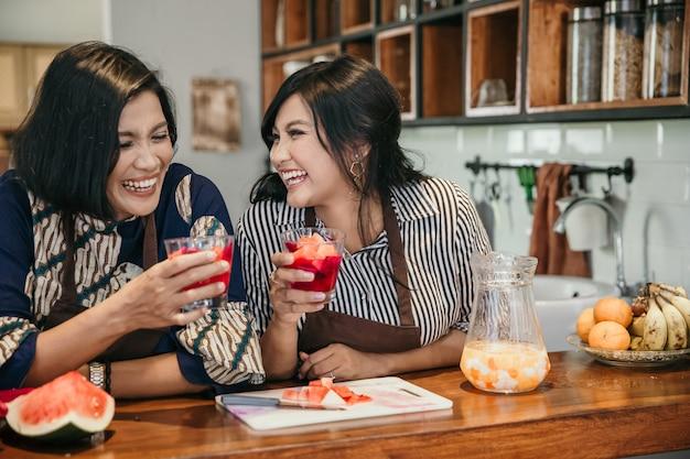Heureuse mère et fille faisant un cocktail de fruits