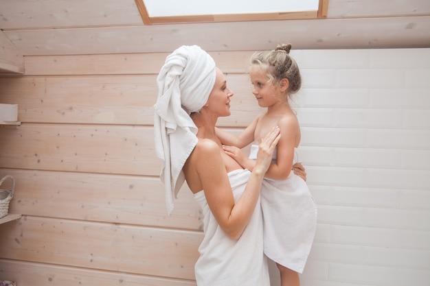 Heureuse mère et fille de famille aimante avec des serviettes, passer du temps ensemble dans la salle de bain blanche.