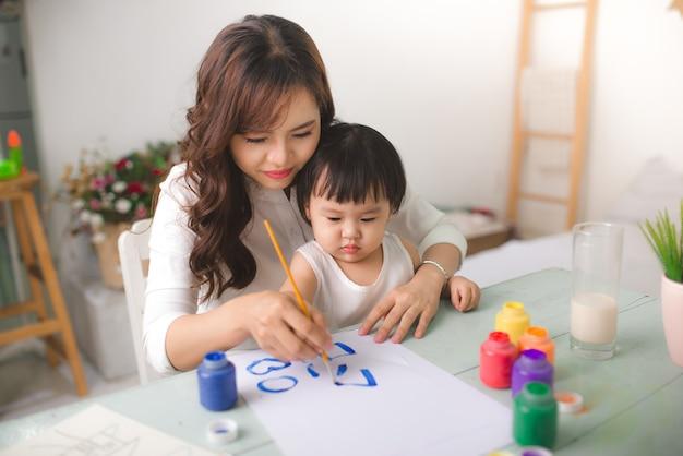 Heureuse mère et fille de famille peignent ensemble. une femme asiatique aide sa petite fille.
