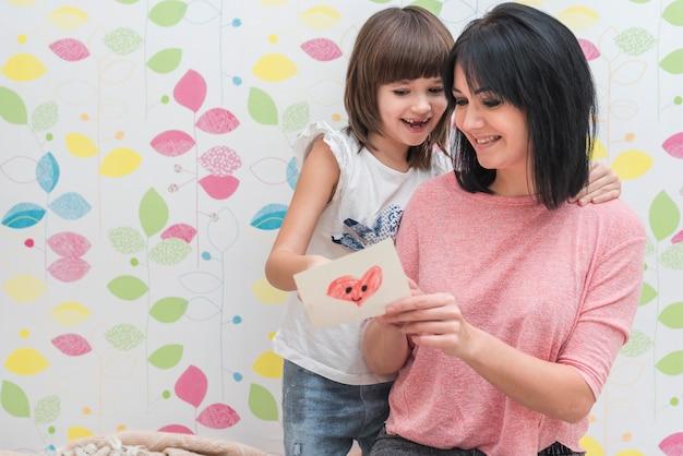 Heureuse mère et fille lisant une carte de voeux
