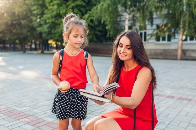 Heureuse mère et fille lisant un livre avant les cours à l'extérieur de l'école primaire. élève prêt pour les cours. éducation