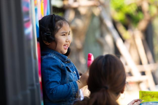 Heureuse mère et fille mangeant des glaces et s'amusant dans le parc par beau matin.