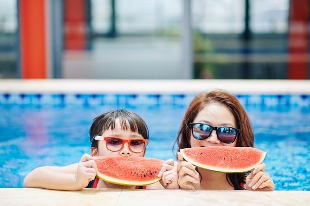 Heureuse mère et fille mangeant de la pastèque après avoir nagé dans la piscine de l'hôtel spa