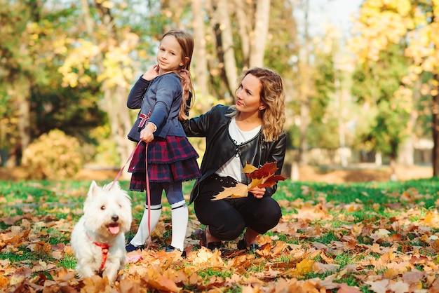 Heureuse mère et fille marchant avec leur chien en automne parc.