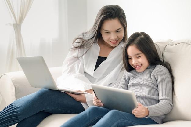 Heureuse mère et fille avec ordinateur portable et tablette