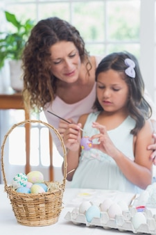 Heureuse mère et fille peignant des oeufs de pâques