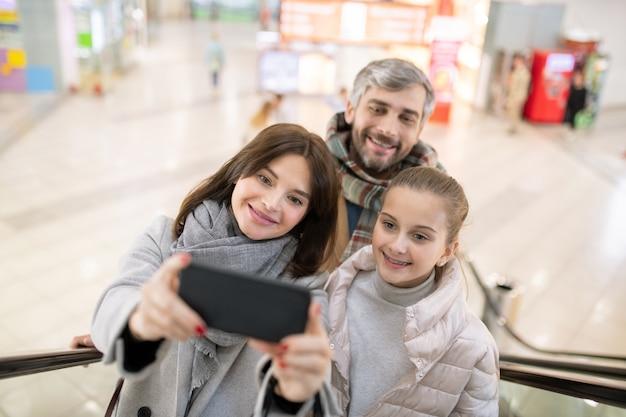 Heureuse mère, fille et père à la recherche de l'appareil photo du smartphone tout en faisant selfie sur l'escalator tout en se déplaçant vers le haut