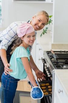 Heureuse mère et fille plaçant le plateau de biscuits au four