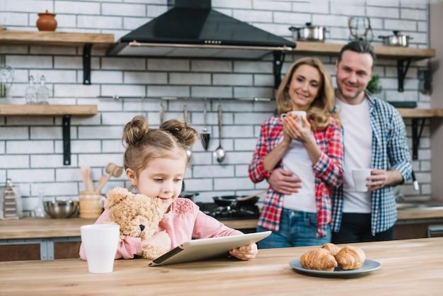 Heureuse mère et fille à la recherche de leur enfant à l'aide de tablette numérique dans la cuisine