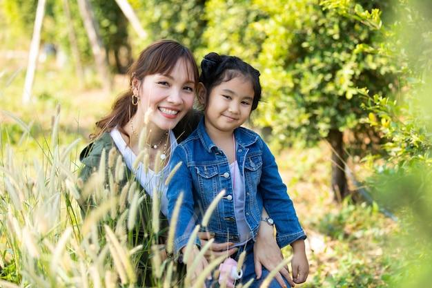 Heureuse mère et fille s'amusant dans le parc par beau matin. concept de famille asiatique heureux