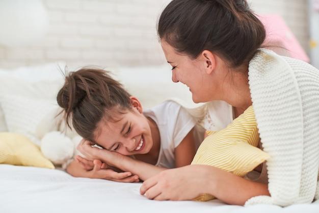 Heureuse mère et fille s'embrassent et rient et s'amusent allongé sur le lit.