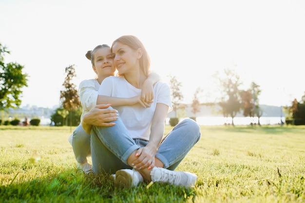 Heureuse mère et fille se détendre dans le parc. scène de nature beauté avec mode de vie en plein air familial au printemps ou en été. heureuse famille élégante se reposant ensemble, s'amusant en plein air.