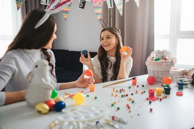 Heureuse mère et fille se préparent pour pâques. fille tenir deux œufs colorés et sourire. la jeune femme regarde la fille et la tient aussi. décoration sur table. les gens dans la chambre.